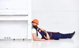 Laderhelling op pianoinstrument De mens met baard, de arbeider in overall en in slaap helm de daling vermoeiden, witte achtergron stock afbeeldingen