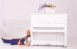Laderhelling op pianoinstrument Lui arbeidersconcept Mens met baard, arbeider in overall en vermoeid in slaap van de helmdaling stock afbeeldingen
