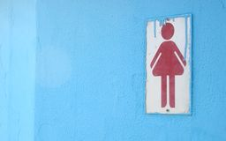 Ladies'. A ladies' toilet sign on blue wall with dripping paint Royalty Free Stock Image