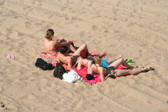 Ladies on the Beach. Four ladies sunbathing on the beach stock image