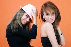 Ladies In Black. Portrait of two young women in black, one wearing a pink hat Stock Photos