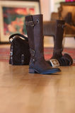 Ladies boots sitting on a wood floor Royalty Free Stock Photos