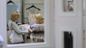 Ladies choosing pajamas and sleepwear in shop stock footage