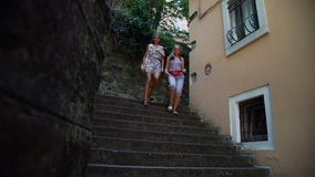 Ladies climb down stone steps walking along narrow street