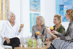 Ladies with cocktails. Four elder ladies talking and sitting with cocktails Stock Photo