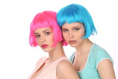 Ladies in colorful wigs and T-shirts posing. Close up. White background Stock Photos