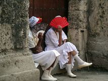 Ladies in cuba (2). Ladies in cuba covering their faces with fans in traditional cuban costumes Stock Image