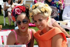 Ladies day. At the races. two women enjoying the sun in high fashion,with a retro look royalty free stock image