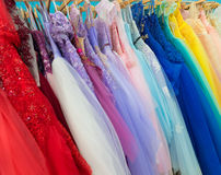 Ladies evening dresses of different colors at shop Stock Photography
