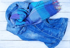 Ladies fashion denim vest and a blue scarf. On a white wooden background Stock Image