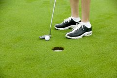 Ladies feet and golf putter Royalty Free Stock Photos