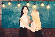 Ladies in formal wear on happy faces, chalkboard on background. Pass exam concept. Attractive students congrats each. Other with success on final exam. Happy stock photo