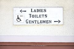 Ladies gentlemen disabled toilets wc sign on plain wall background. uk England London royalty free stock images