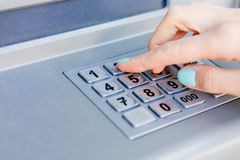 Ladies hand dials the PIN code at an ATM Royalty Free Stock Photo