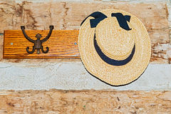 Ladies hat hanging on the hanger in old farm house. Wall with a hanger and ladies hat hanging on it Stock Photos