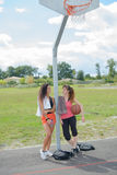 Ladies leaning against post basketball net. Ladies leaning against post of basketball net Royalty Free Stock Photos