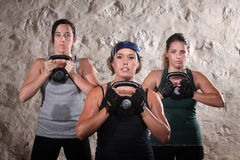 Ladies Lifting Kettlebells in Workout