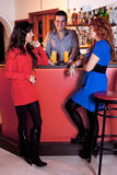 Ladies Night Out. Two pretty young stylish female friends standing laughing with the bartender at the counter in a bar Stock Photography