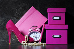 Ladies pink female office desk. Ladies pretty pink female office desk with high heel shoe, clock, pen, stationery filing boses, pearls and diary organiser Royalty Free Stock Image