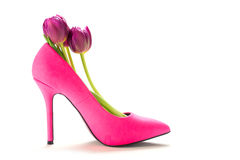 Ladies pink high heel shoe with tulips inside, isolated on white. Ladies pink high heel shoe in profile with tulips inside, isolated with shadows on a white stock photo
