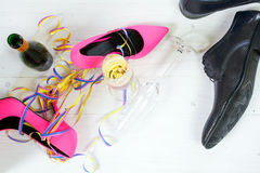 Ladies pink high heela and black mens shoes lying between champa Stock Images