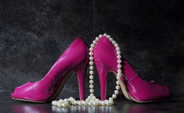 Ladies pink high heels with long strand of white pears against a Royalty Free Stock Photos