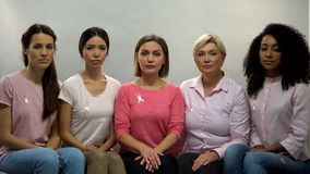 Ladies with pink ribbons looking in camera, moral support breast cancer patients. Stock photo stock image