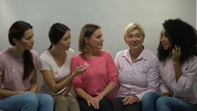 Ladies with pink ribbons talking, group of support breast cancer patients health. Stock footage stock video footage