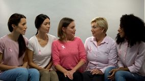 Ladies with pink ribbons talking, group of support breast cancer patients health. Stock photo royalty free stock images