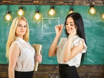 Ladies ready to start private lesson, chalkboard on background. Attractive teachers overworking after classes. Teachers. In formal wear with book and glasses stock image