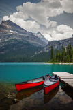 Ladies in Red. Red canoes seem perfectly placed and waiting at Lake O'Hara in Yoho National Park, Canadian Rockies, British Columbia Royalty Free Stock Photo