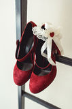 Ladies red chamois leather pumps shoes on a metal fire ladder at the balcony. brides accessories in a wedding day Stock Images