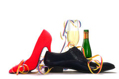 Ladies red high heels and black men's shoes with champagne and s. Treamers, concept for gender topics such as party, dating, flirting, love affair,  with shadows Royalty Free Stock Image