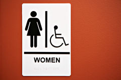 Ladies Room Sign on the Wall. Ladies Room Sign on on Orange Colored Wall royalty free stock image