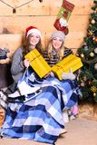 Ladies in Santa hats hold yellow presents for xmas. Girls with happy faces near Christmas tree on wooden wall background. Women with gift boxes, ice skates and stock photography