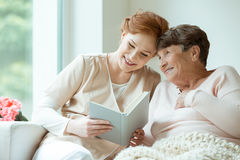 Ladies sitting on the couch. Two ladies sitting on the couch and reading a book in hospice room Stock Photo