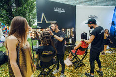 Ladies sitting in a pop-up beauty salon with hairstylist during popular outdoor festival. KYIV, UKRAINE - JUL 23: Ladies sitting in a pop-up beauty salon with Royalty Free Stock Photos