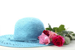 Ladies sun hat and roses. On a white wood table for International Womens Day, March 8 Royalty Free Stock Photos