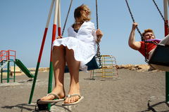 Ladies on a swing. Mother and daugther on a swing enjoying their vacation on a beach Stock Images