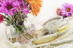 Ladies Tea Party. A beautiful bright ladies tea party with cup of tea, lemon biscotti and fresh flowers, copy space Royalty Free Stock Images