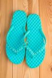 Ladies turquoise flip flops on the wooden floor Royalty Free Stock Photos