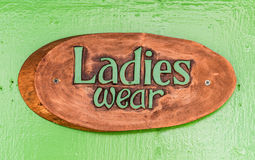 Ladies Wear sign with text. Wooden plate with written LADIES WEAR on green painted background Royalty Free Stock Photo