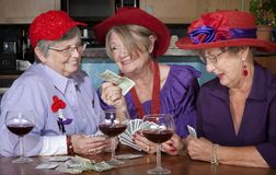 Ladies wearing red hats playing cards Royalty Free Stock Images