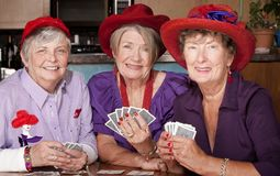 Ladies wearing red hats playing cards Royalty Free Stock Image
