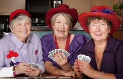 Ladies wearing red hats playing cards Stock Image