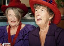 Ladies wearing red hats playing cards Royalty Free Stock Photo