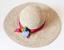 Ladies` wide brim straw hat with red band. And textile flower on white background Stock Image
