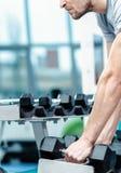 Lading op de bicepsen Succesvolle atleet die met domoor uitwerken Royalty-vrije Stock Afbeeldingen