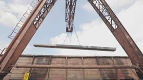 Lading van een profielpijp door een brugkraan in een goederenwagon, ladingenmetaal in een pakhuis, een grote brugkraan