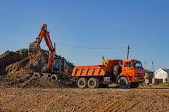 Lading van land met een graafwerktuig in een stortplaatsvrachtwagen stock foto's